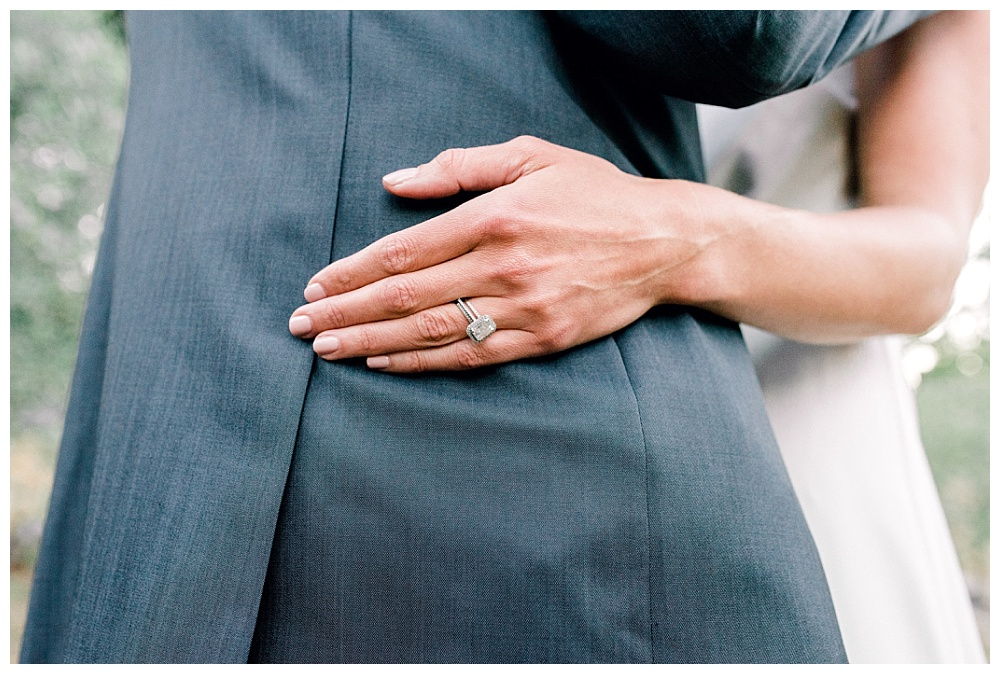 bride's hand on groom's back showing off beautiful wedding ring, hand contrasts with groom's slate blue suit