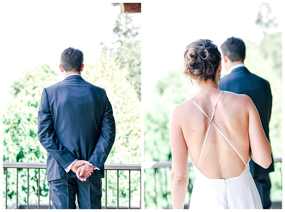 bride sneaking up on the groom for their first look on a balcony overlooking a vineyard