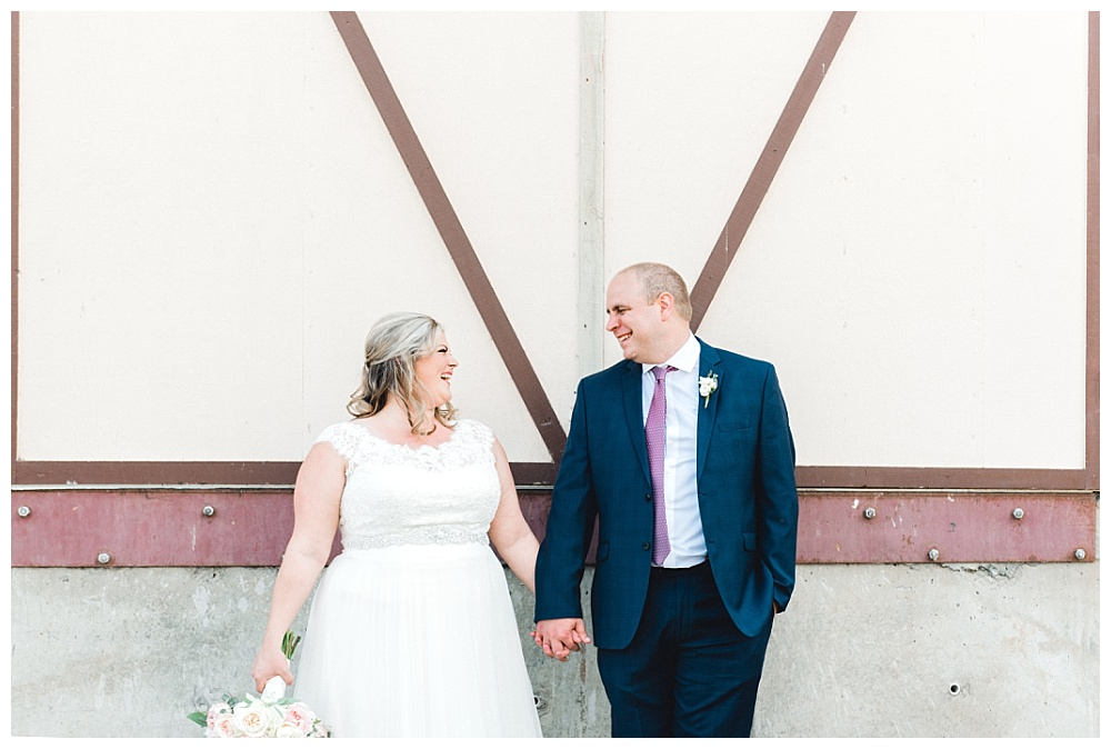 bride and groom portrait looking at one another in front winery loading dock
