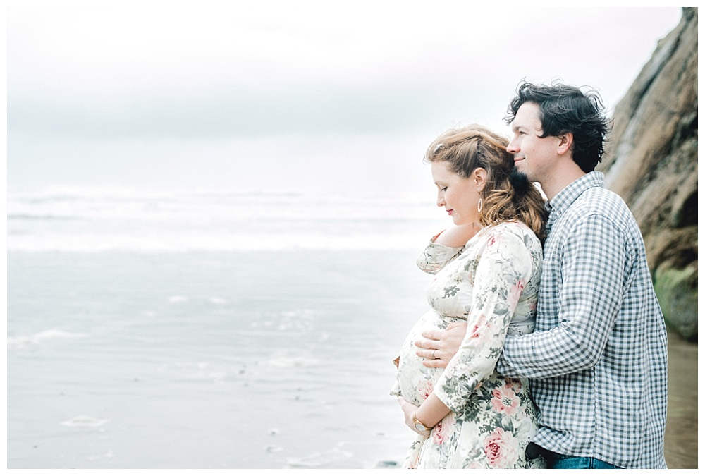 husband embracing pregnant wife in floral dress while tide rolls in on the Oregon Coast