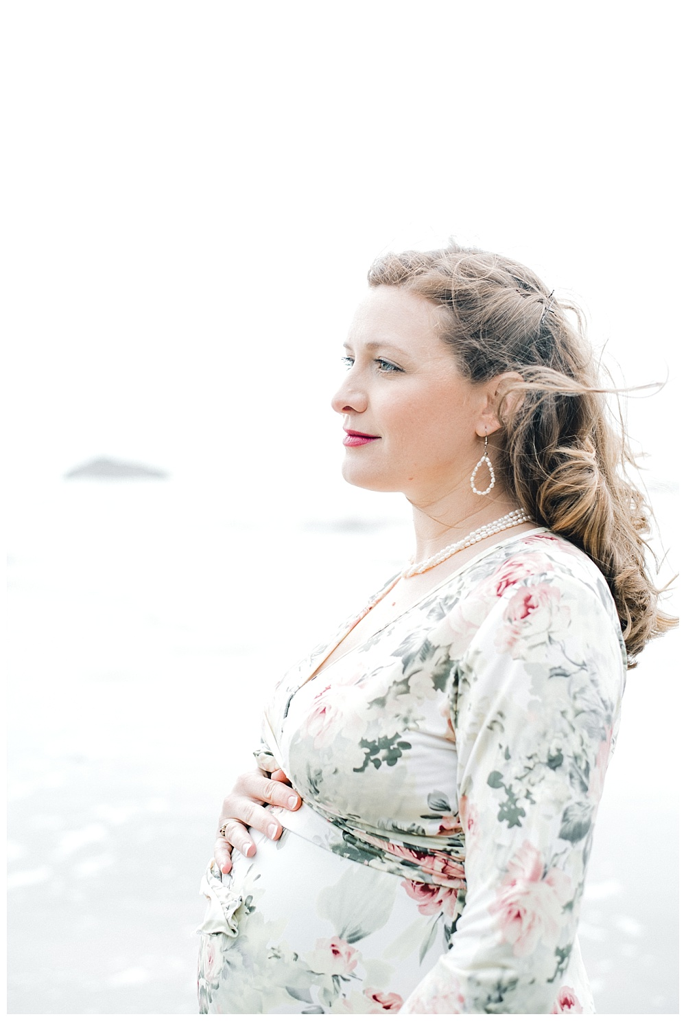 maternity portraits of red haired woman on oregon coast in floral dress cradling belly