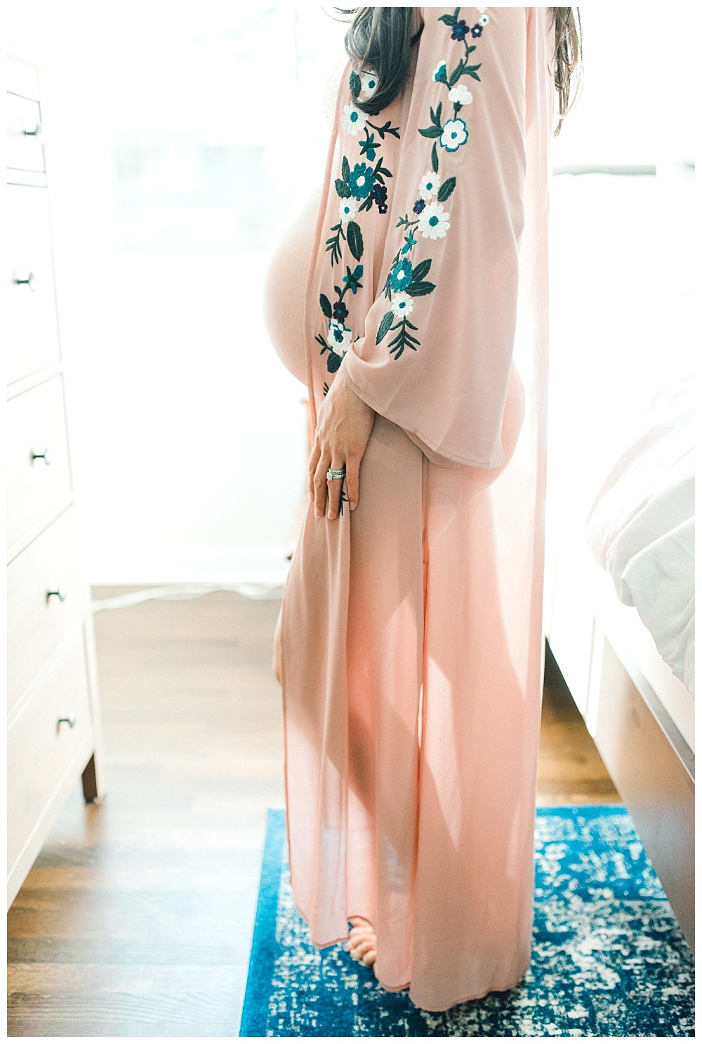pregnant mother in bedroom with pink kimono showing belly