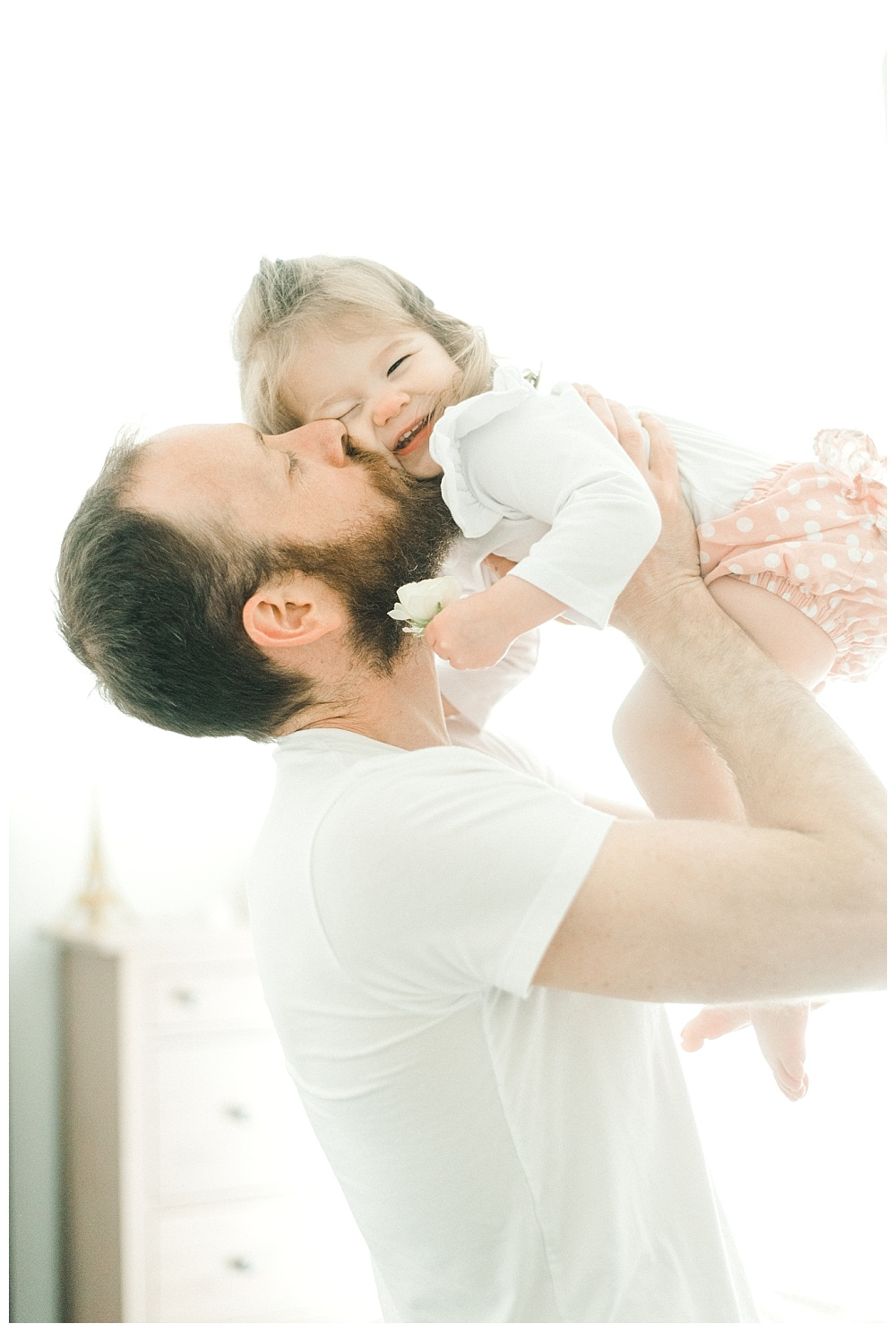 father kissing daughter in light-filled bedroom