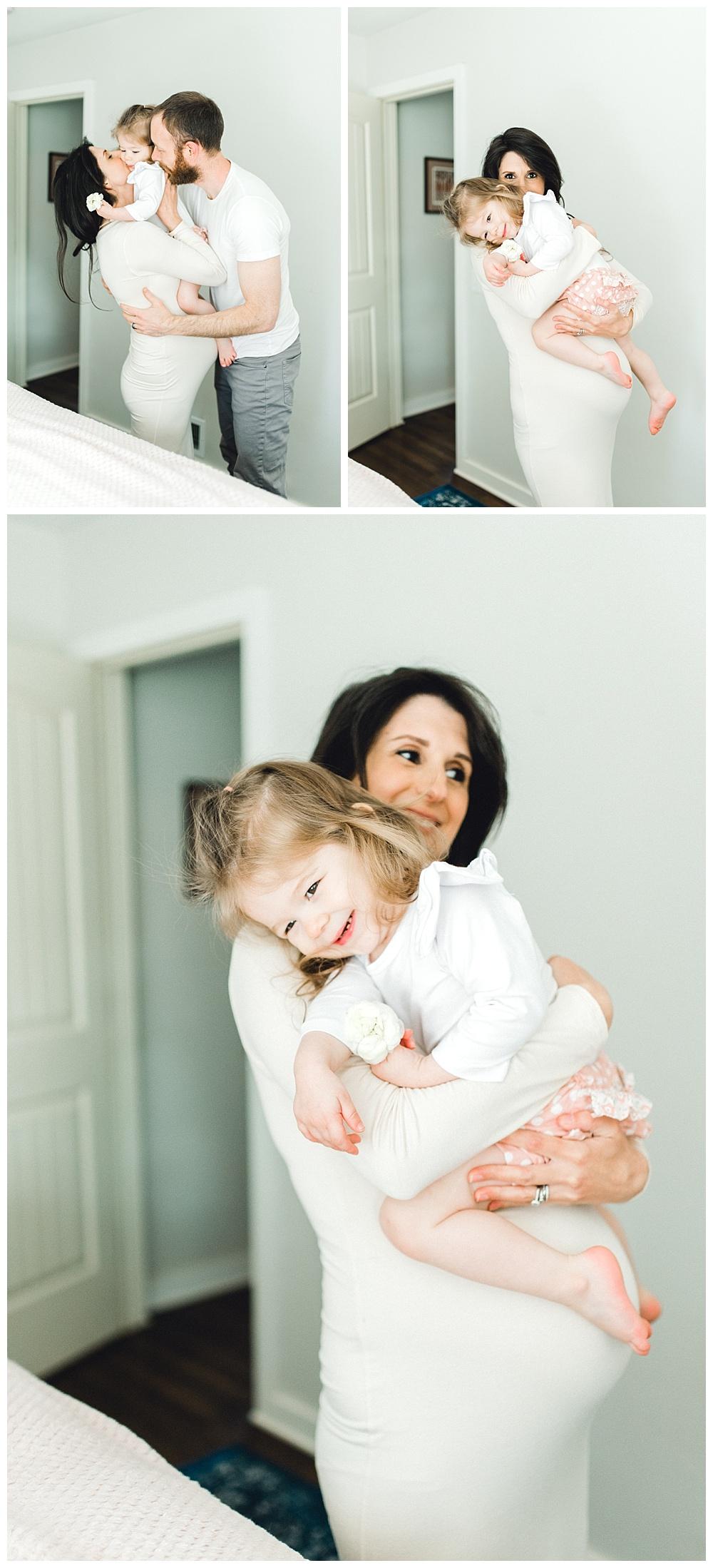 pregnant mother cradling her toddler girl in bedroom
