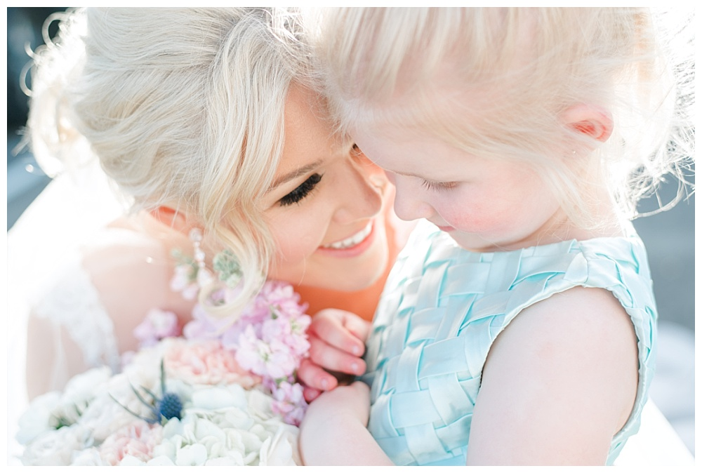 bride and flower girl snuggling tight for a photo