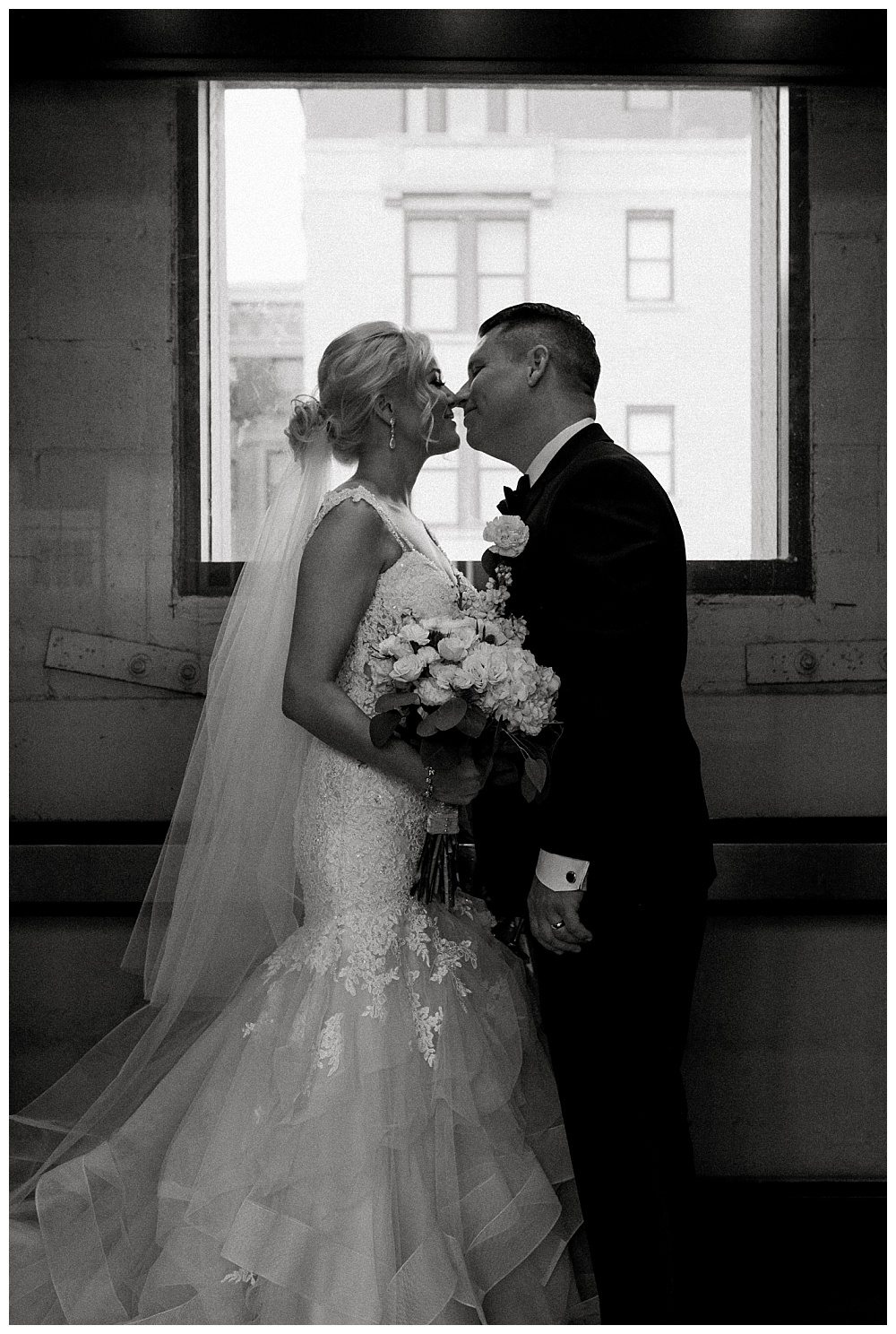 bride and groom kissing in a downtown elevator