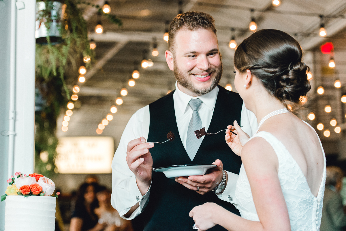 bride and groom eating cake at coopers hall with romantic string lighting overhead, at portland's coopers hall wedding venue and winery.