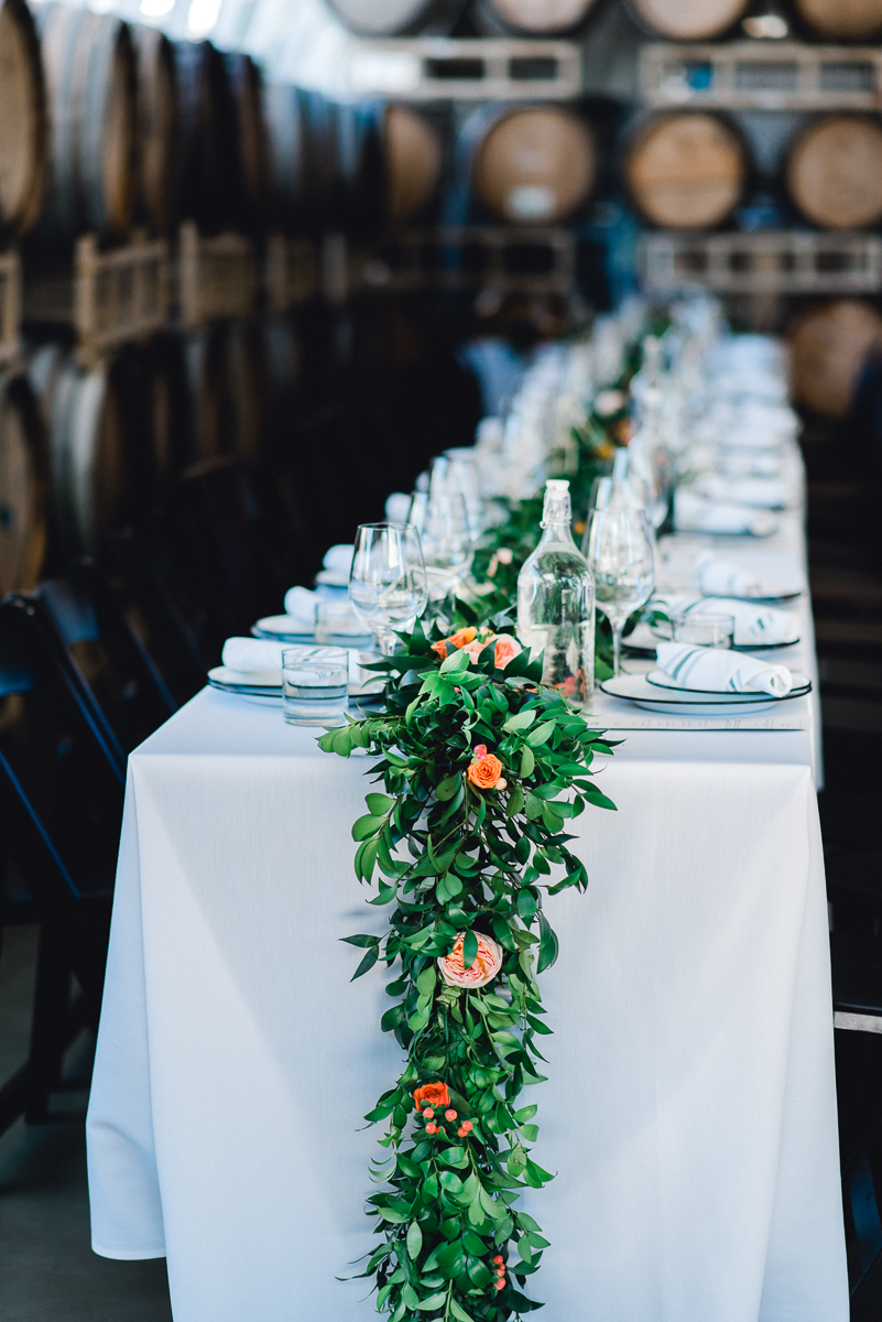 wedding reception table settings and garland against a backdrop of wine barrels at coopers hall wedding venue and winery in downtown Portland Oregon