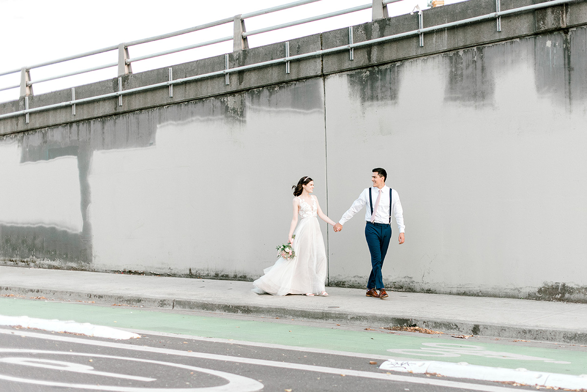 groom leading bride while holding hands down urban street setting in downtown portland oregon's central eastside industrial district.